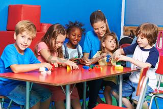 Kinder und Lehrerin bauen mit Bausteinen