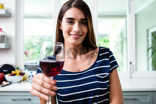 Portrait of smiling young woman holding red wine glass