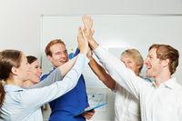 Business Team gibt sich High Five im Büro