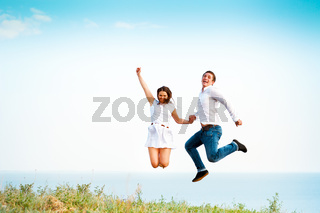 Young happy couple jumping on the beach