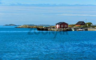 Holzhaus am Ufer einer Bucht bei Bud