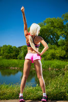 Sexy sport in nature. Blonde girl in the woods near the water does sports exercises in short shorts
