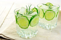 Lemonade with cucumber and rosemary in two glassful on napkin