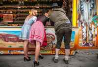 Two lovely girls, one man playing shooting games and having fun at German funfair Oktoberfest. Wearing traditional Dirndl dresses from back