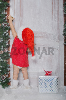 Girl dressed as Santa opens door under snow