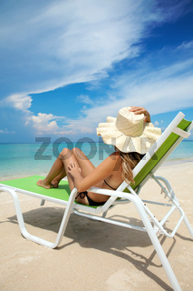 Young woman with hat relaxing on a deck chair