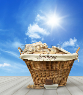 Laundry basket with clothes on rustic table against blue sky