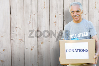 Composite image of happy volunteer senior holding donation box