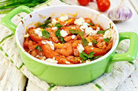 Shrimp and tomatoes with feta in pan on board