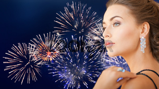 beautiful woman with diamond earring over firework