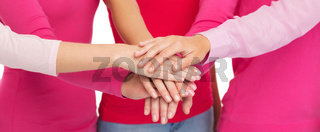 close up of women in pink shirts with hands on top