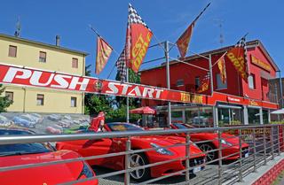 rote Sportwagen vor rotem Haus
