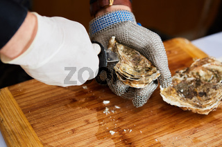 Fresh oyster held open with knife in hand