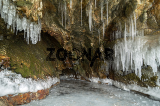 Multicolored stone cave in the cliff with icicles.