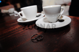 two silver wedding rings background cups of coffee