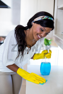 Happy woman cleaning the kitchen