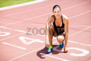 Portrait of female athlete kneeling on running track