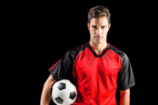 Portrait of confident male athlete holding football