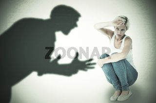 Composite image of crouching sad woman holding her hand