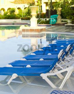 Empty beach chairs near  pool