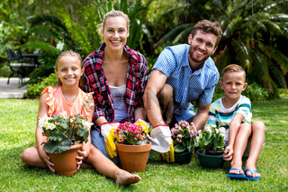 Smiling family with flower pots on grass at yard