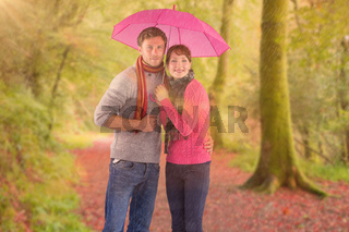 Composite image of couple standing underneath an umbrella