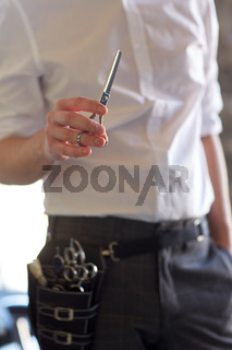 close up of male stylist with scissors at salon