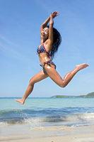 Attractive woman in bikini jumping on the sea beach