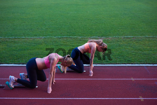 woman group  running on athletics race track from start