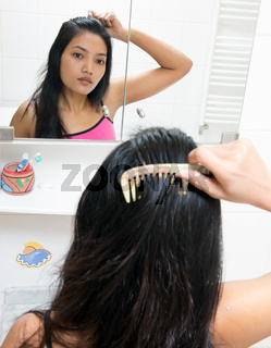 Young woman combs her hair