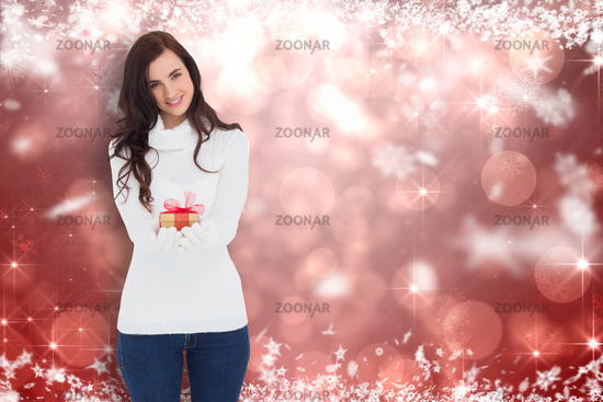 Composite image of smiling brunette in white gloves holding gift