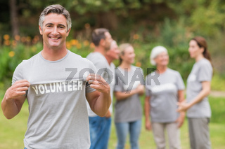 Happy volunteer showing his t-shirt to camera