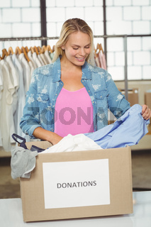 Woman separating clothes from donation box in office