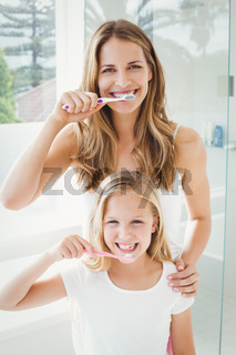 Portrait of smiling mother and daughter brushing teeth