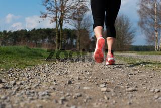 joggerin läuft auf einem schotterweg