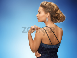 beautiful woman with diamond earring over blue