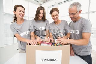 Smiling volunteers sorting donation box