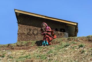 Oromo Frau sitzt vor ihrem Wohnhaus