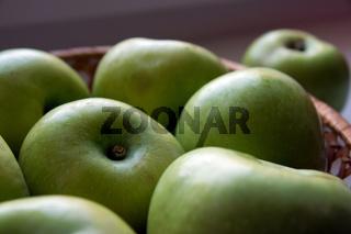 Green apples, lying in a basket
