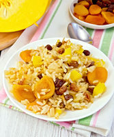 Pilaf fruit with pumpkin in white plate on light board