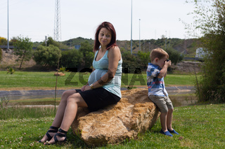 Pregnant woman and child boy sitting outdoors