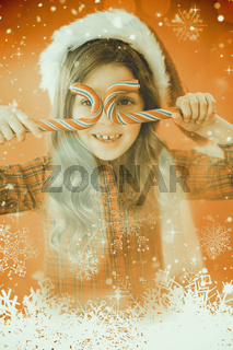 Composite image of happy little girl in santa hat holding candy canes