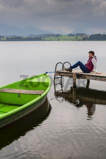 Frau 50+, Holzsteg, grünes Ruderboot, Hopfensee, Hopfen am See, bei Füssen, Ostallgäu, Allgäu, Bayern, Deutschland, Europa