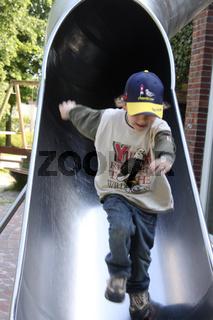 Kleiner Junge auf einer Rutsche