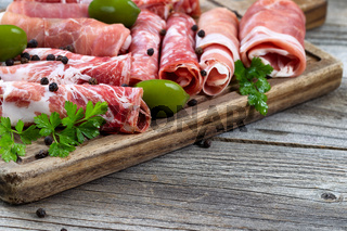 Various raw meats on serving board with rustic background