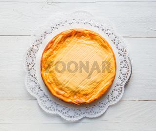 Käsekuchen auf weißem Holz mit Tortenspitze
