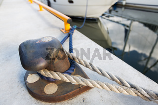 rusted iron mooring bollard with rope on pier