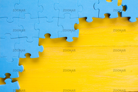 Puzzle on yellow wooden background