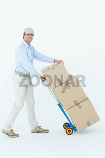 Happy delivery man pushing trolley of cardboard boxes