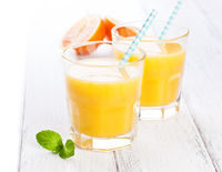 Summer yellow orange lemonade in glass with blood oranges and straw on a wooden table